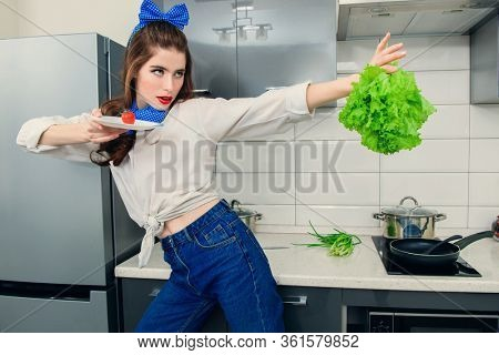 An attractive girl in everyday clothes is cooking in the kitchen. Cooking in the kitchen. Gastronomic concept.