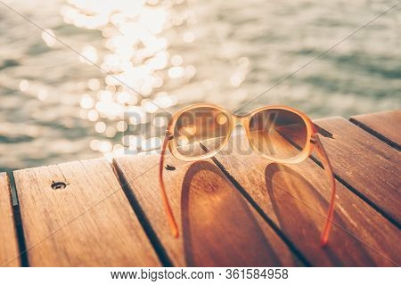 Sunglasses At The Wooden Pier During Sunset. Luxury Vacation Resort. Holiday Getaway Concept. Horizo