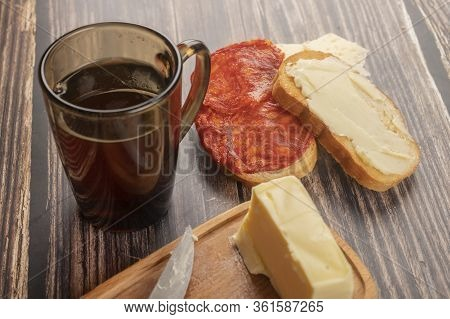 A Wooden Butter Dish With A Piece Of Butter, Fresh Wheat Toast With Butter, Sausage And Cheese, And