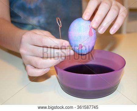 Child Hands Holding Easter Egg Over Purple Dye