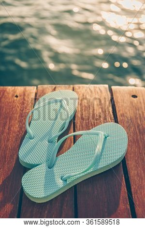 Flip Flops At The Wooden Pier During Sunset. Luxury Vacation Resort. Holiday Getaway Concept. Vertic