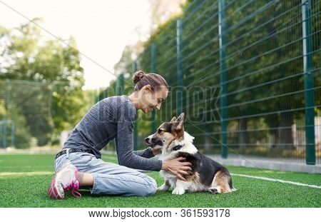 Young Female Owner Sitting On The Grass And Petting The Dog. Spending Time Together.