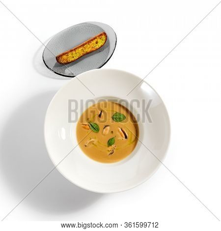 Chilean mussels soup in white bowl. Served main course top view. Seafood cream soup with roasted bread slice. Restaurant food portion, main course with toast. Dinner, gourmet meal in plate