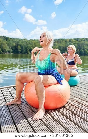 Two senior women with exercise ball doing a back exercises at the lake