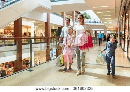 Happy family shopping with many shopping bags in shopping mall