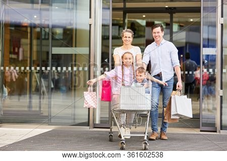 Happy family after shopping with shopping cart and shopping bags