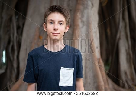 Young boy posing in summer park with ficus trees. Cute spectacled smiling happy teen boy 13 years old, looking at camera over roots. Kid's outdoor portrait.