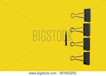 Four Black Big Paper Clips For Office Stationery Lying Against Small Pencil On A Yellow Background.