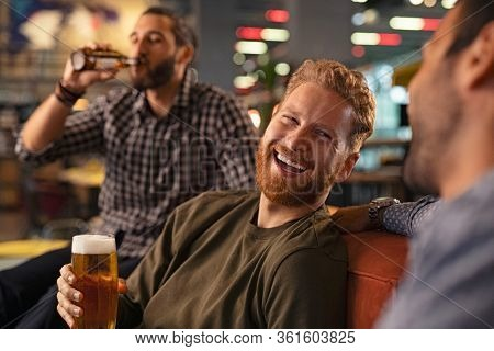 Group of men friends enjoying night out at rooftop bar. Old friends having fun and drinking draft beer at pub. Group of three men drinking fresh beer and having conversation during evening at pub.