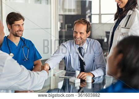 Businessman shaking hands with doctor in meeting room. Doctor and representative pharmaceutical shaking hands in medical office. Salesman with new medicines shaking hands in hospital with medical team