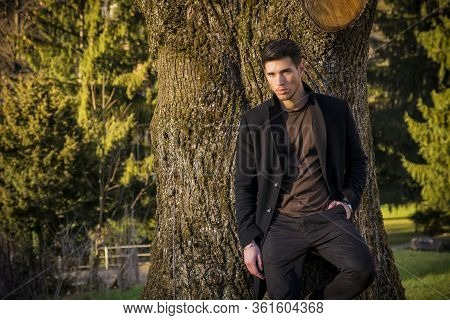 Handsome Young Man Leaning Against Tree Wearing Coat