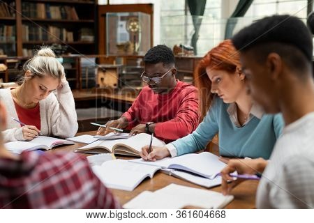 Group of university students doing class assignment in the library. Multiethnic young men and women reading reference books for study. Group of college students studying for exam at college library.