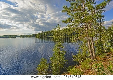 Sun And Clouds In The North Woods On Saganagons Lake In Quetico Provincial Park In Ontario