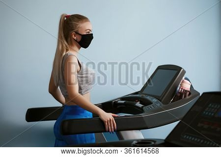 A Pretty Girl In A Protective Mask Is Engaged On A Cardio Simulator.protective Masks Against Virus I