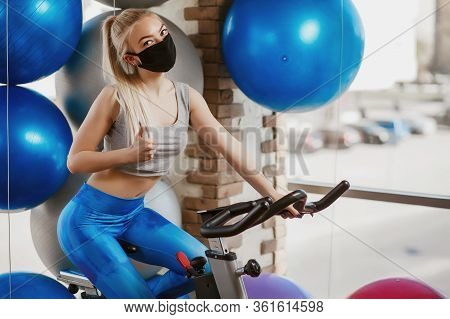 A Pretty Girl In A Protective Mask Is Engaged In An Exercise Bike. Protective Masks Against Virus In