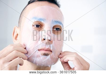closeup of a handsome caucasian man applying or removing a bio-cellulose sheet mask to his own face
