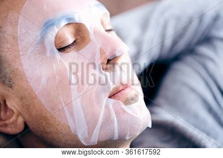 closeup of a handsome caucasian man wearing a bio-cellulose sheet mask while is relaxing