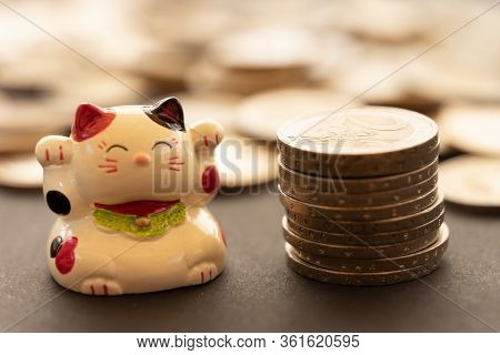 Maneki Neko Or Beckoning With A Coin Stack, And More Unfocused Coins On The Background.. Conceptual