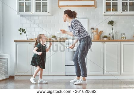 Happy mother's day! Child daughter and mom cooking and having fun in the kitchen at home. Family holiday and togetherness.