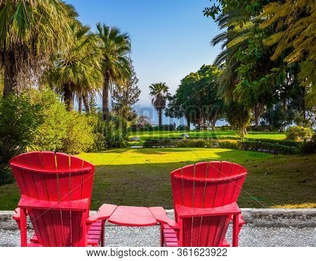 Catholic Church of the Beatitudes and park around the monastery. Two red chairs - deck chairs on the platform for relaxing. The concept of religious pilgrimage and photo tourism