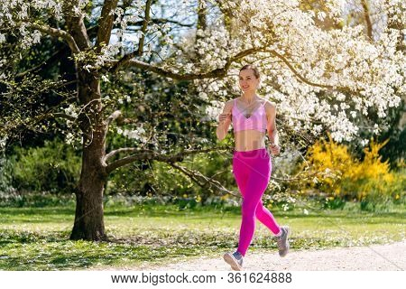 Woman running in spring park thru blossoming trees