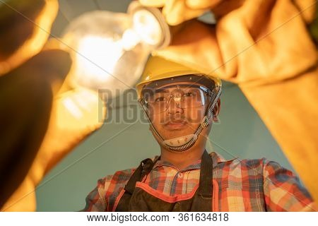 Electrician With Light Bulbs,electrician Fixing The Light Inside Remodeled At Home.