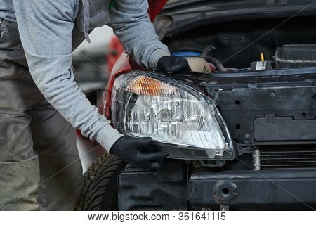 Auto service. Technician assembling an automobile headlight lamp. bodywork repair for insurance