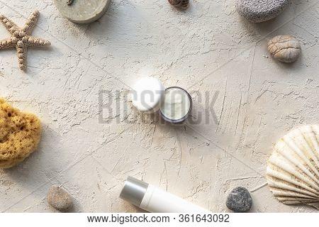 Face Cream In White Jar, Natural Soap, Sea Sponge And Pumice Stone On White Plaster Background. Natu