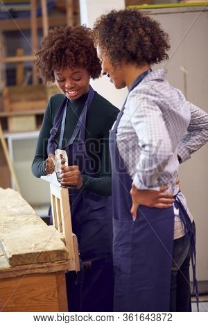 Tutor With Female Carpentry Student In Workshop Studying For Apprenticeship At College Planing Wood