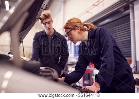 Male And Female Students Looking At Car Engine On Auto Mechanic Apprenticeship Course At College