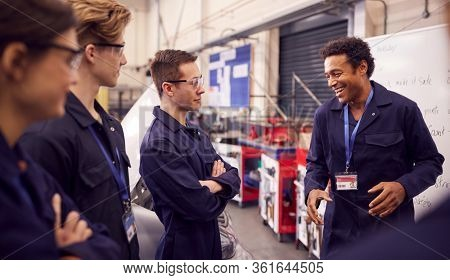 Male Tutor By Whiteboard With Students Teaching Auto Mechanic Apprenticeship At College