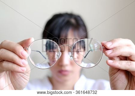 Short-sighted Woman Is Holding Glasses In Hand With White Background. Symbolic Photo For Bad Vision