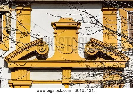 Yellow Pediment Over A Doorway In Curved And Broken-apex Style. The Opening In The Middle Is Facial-