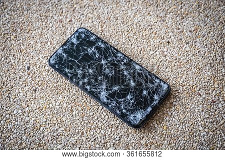 Closeup Of Modern Mobile Smart Phone With Broken, Cracked Screen On Stone Floor Background. Select F