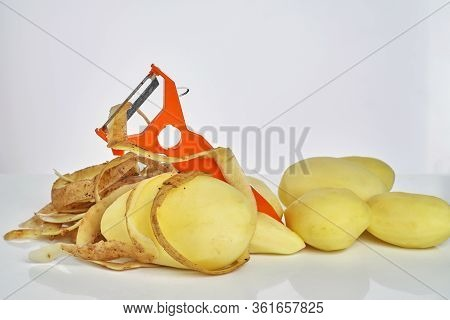 Peeled Raw Potato, Peel Peel The Potatoes And Orange Tool For Cleaning Of Vegetables On A White Back