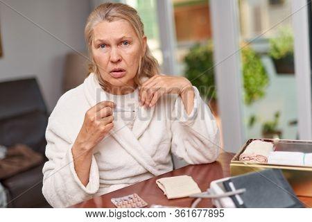Sickness, Seasonal Virus Problem Concept. Worried Elderly Woman Measures The Temperature Of The Hous