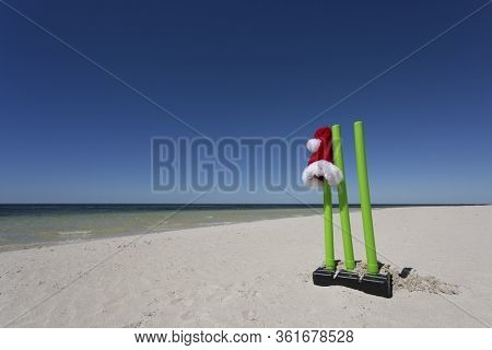 A Santa Hat Perched On Cricket Wickets At The Beach.