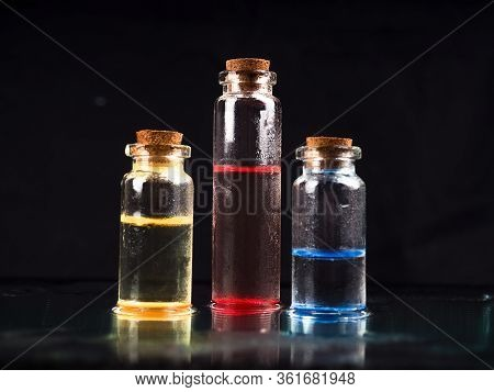 Three Colourful Liquid Glass Vial With Black Background For Medical Research. In A Chemistry Laborat