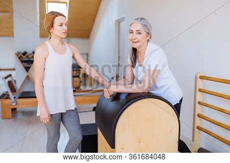 Young Professional Instructor Helping An Elderly Woman Cant Workout Independently Doing Stretching B