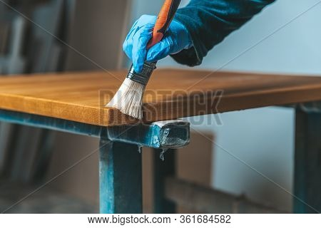 Coating Of Wooden Surface With Protective Varnish. Hand In Blue Rubber Glove Uses Brush