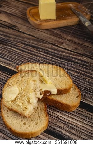 Fresh Wheat Toast With Butter And A Wooden Butter Dish With A Piece Of Butter On A Wooden Background