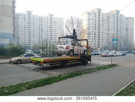 Kiev, Ukraine April 17, 2020 - A Tow Truck At A Pedestrian Crossing Immerses A Car That Was Parked I