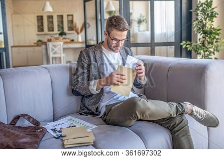 Stylish Fair-haired Man Sitting Pon The Sofe With Envelope In His Hand