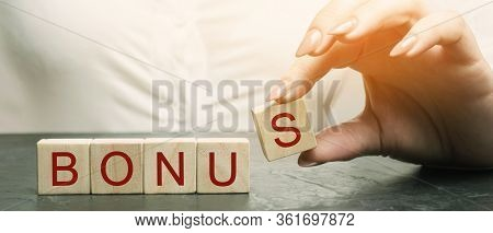 Woman Puts Wooden Blocks With The Word Bonus. Receive Bonuses, Rewards And Preferences. Getting Bene