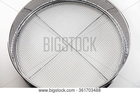 Screening. A chrome sieve or screen used for filtering wanted or unwanted elements. Also called mesh strainer or sift. Focus at center of screen net.