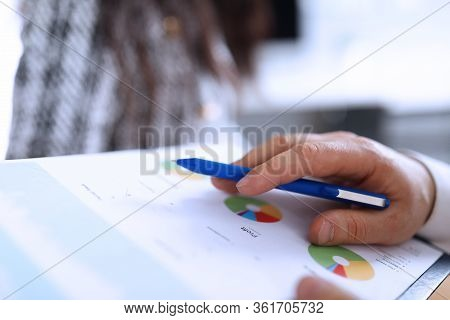 Male Hands Hold Financial Statement Profit And Pen. Reliable And Functional Financial Management Sys
