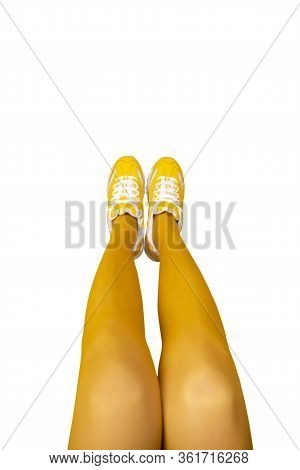New Yellow Female Sneakers On Long Woman Legs In Yellow Tights Isolated On White Background. Monochr