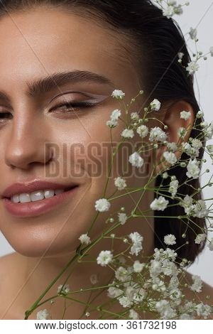 Close Up Portrait Of A Face With Beautiful Skin And Nude Makeup, Eyeliner And Long Eyelashes, Puffy