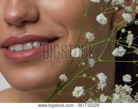 Macro Photo Of Female Lips With Beautiful Skin And Nude Makeup. Light Transparent Gloss On Full Lips
