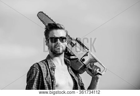 Barbershop Concept. Dangerous Job. Powerful Chainsaw. Lumberjack Hold Chainsaw. Masculinity Concept.